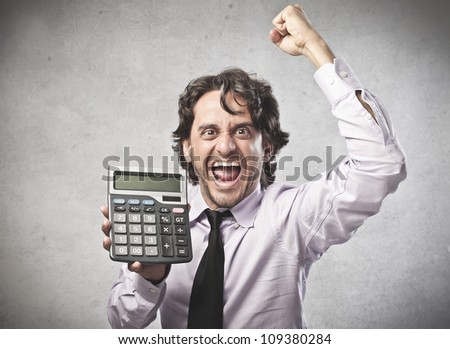 Triumphing businessman showing a calculator