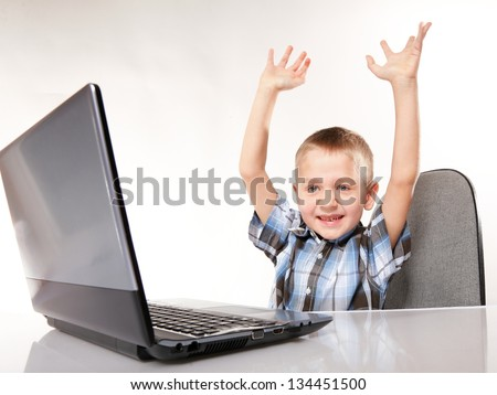 Triumphing child boy with a laptop notebook computer isolated on white background. Computer addiction. - stock photo