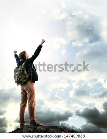 Triumphing young man on the top of mountain  - stock photo