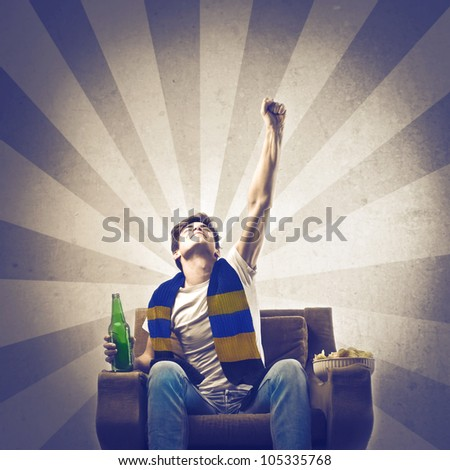Triumphing young supporter wearing his league's scarf - stock photo