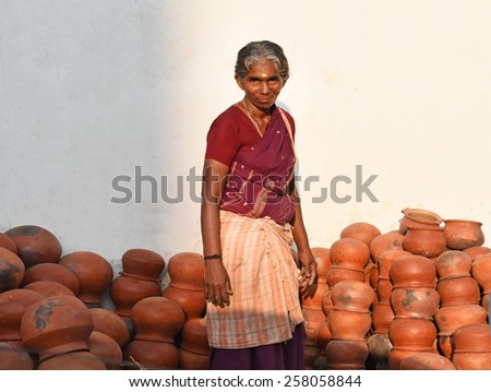 TRIVANDRUM, KERALA, INDIA, MARCH 04, 2015: Woman Entrepreneur. Woman power. Woman empowerment. Bread winner of the family. A middle aged lady sells pots during Attukal ponkala in the morning. - stock photo