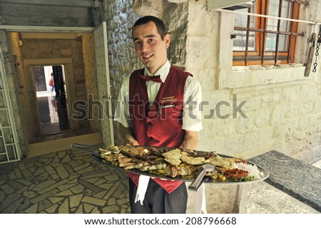 TROGIR, CROATIA, MAY 27, 2011. A young Croatian waiter with a suit and a big plate of different kinds of meat and big chips, in Trogir, Croatia, on May 27th, 2011.