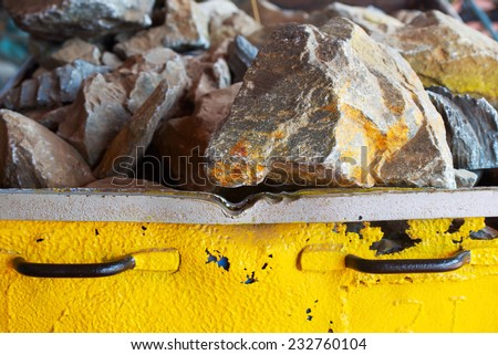 Trolley with gold ore in the gold mine - stock photo
