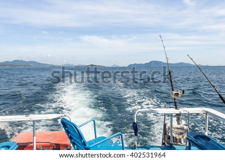 Trolling fishing boat rod and golden saltwater reels deep blue ocean sea wake - stock photo