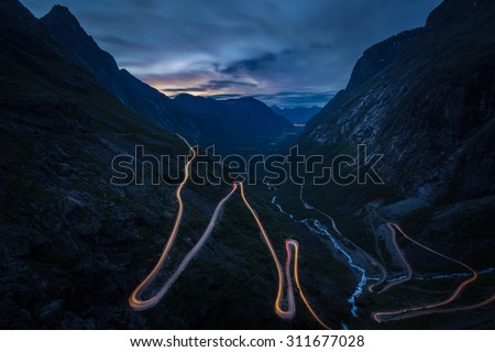 Trollstigen, Andalsnes, Norway. The famous road of Trollstigen during night with cars passing trough. - stock photo