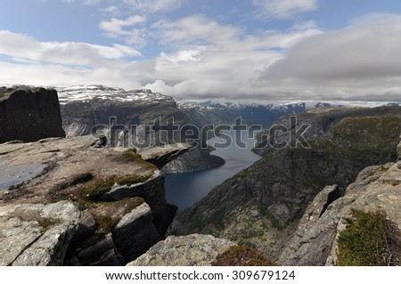 Trolltunga (Troll's tongue) is a piece of rock jutting horizontally out of a mountain about 700 metres above the north side of the lake Ringedalsvatnet near of Odda in Hordaland county, Norway. - stock photo