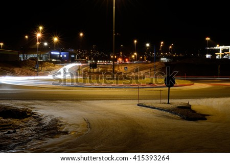TROMSOE, NORWAY - FEBRUARY 6, 2014: heavy car traffic on Langnes roundabout with public buildings in the background - stock photo