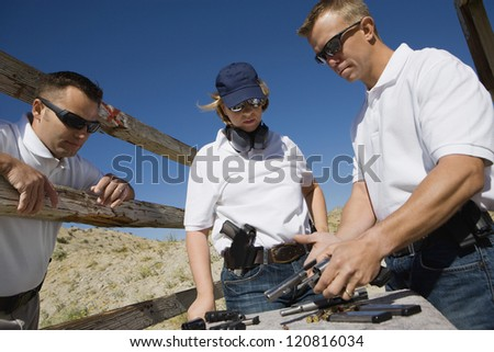 Troops reloading pistols at shooting range - stock photo