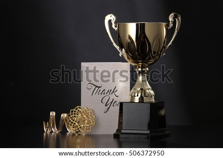 trophy with greeting card on top table
