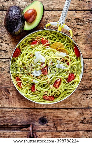 Tropical avocado, tomato and parmesan Italian noodles or pasta garnished with lemon on an old rustic wooden table with a fresh ripe halved avocado pear to the side, overhead view - stock photo