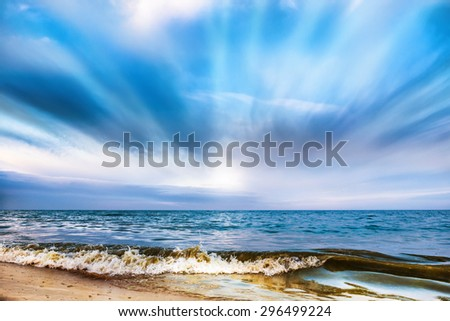 Tropical beach and blue sea with waves, white clouds on background - stock photo