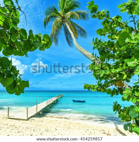 Tropical beach in Dominican Republic. Blue fishing boat. Fishing boat at wooden pier.