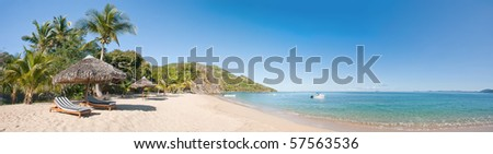 Tropical beach panorama with deckchairs, umbrellas, boats and palm tree - stock photo