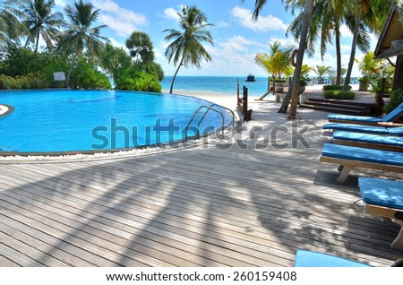 Tropical beach resort hotel swimming pool -- Tropical beach vacation and travel concept  - stock photo