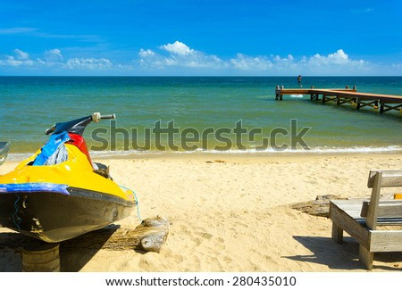 Tropical beach scene with personal water craft - stock photo