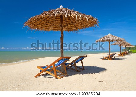 Tropical beach scenery with parasols in Thailand - stock photo