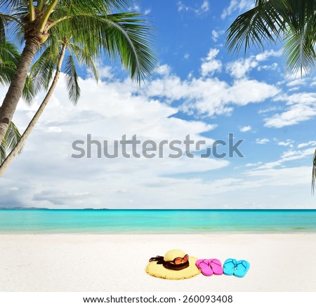 Tropical beach vacation and travel concept -- Sunhat with sunglasses and flip flops on white sandy beach  - stock photo
