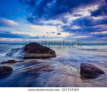 Tropical beach vacation background - waves and rocks on beach of sunset - stock photo