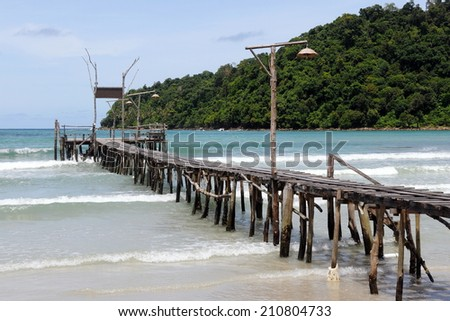 Tropical Beach View of an Old Wooden Pier Leading out to Sea