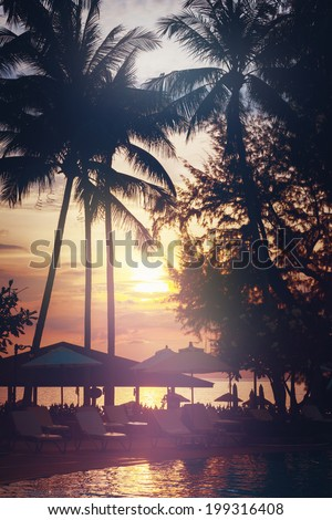 Tropical beach view. Palm trees and sunset sky. Recreation area with sun umbrellas. - stock photo