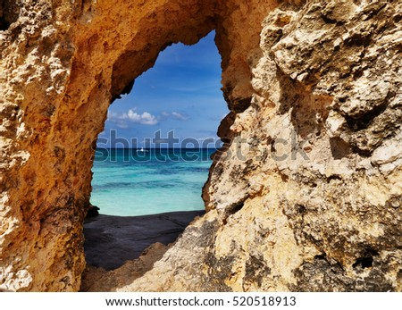Tropical beach, view through a hole in the rock, Boracay island, Philippines