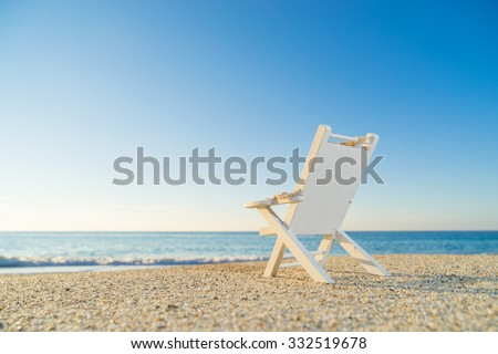 tropical beach with a sun-lounger facing the blue sea at dawn - shallow DOF - stock photo