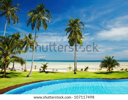 Tropical beach with coconut palms and swimming pool - stock photo