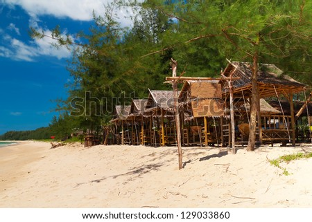 Tropical beach with huts in Thailand - stock photo