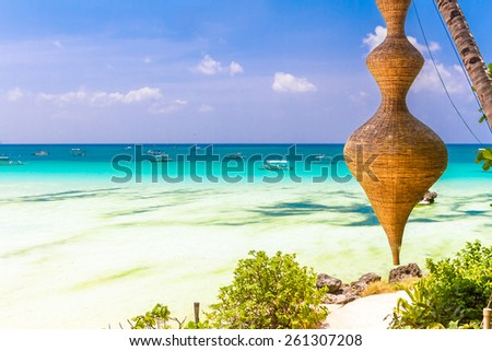 tropical beach with palm trees and beach beds, summer vacations - stock photo