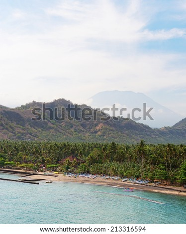 Tropical beach with palms and boats and big volcano on background on Bali in Candidasa, Indonesia - stock photo