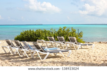 Tropical beach with sun loungers and turquoise ocean. Resort on Bahamas