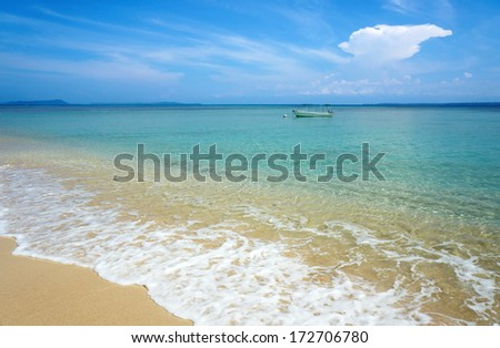 Tropical beach with turquoise water and a boat alone in the Caribbean sea, Zapatillas islands, Panama - stock photo