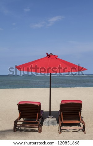 Tropical beach with two red umbrellas