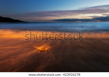 Tropical beach with volcanic sand after sunset in light of the lanterns on the shore Tenerife, Canary Islands, Spain  - stock photo