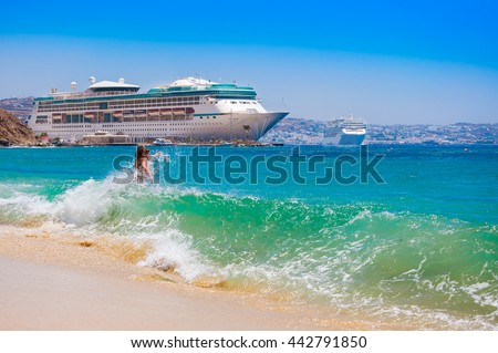Tropical beach with waves  and cruise ship in distance - stock photo