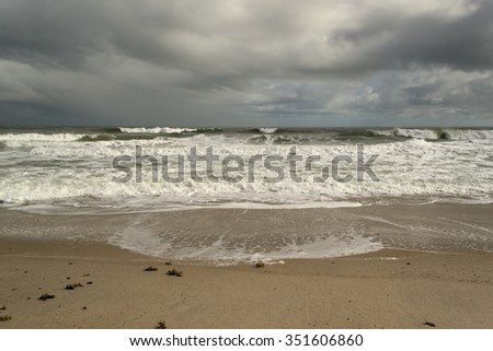 Tropical beach with waves breaking and stormy dark sky - cape Canaveral