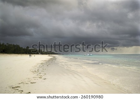 Tropical beach with white sand and dark storm clouds - stock photo