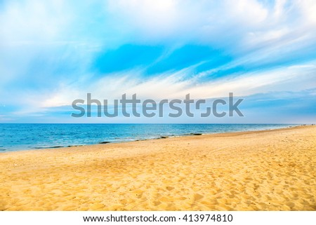 Tropical beach with yellow sand and blue sea with waves, white clouds on background - stock photo