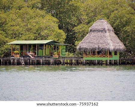 Tropical bungalow over the sea with mangrove trees in background, Caribbean, Bocas del Toro, Panama - stock photo