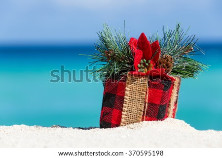 Tropical celebration on beach. Present box on sand against turquoise caribbean sea water - stock photo