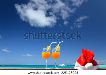Tropical christmas holidays --  Two glasses of tropical fruit juice and red santa hat near the beautiful tropical sea - stock photo
