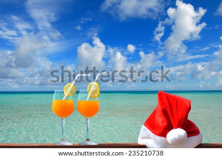 Tropical christmas vacations -- Two glasses of tropical fruit juice and red santa hat near the tropical green lagoon - stock photo