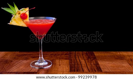 tropical cocktail isolated on a black background served on a bar top - stock photo