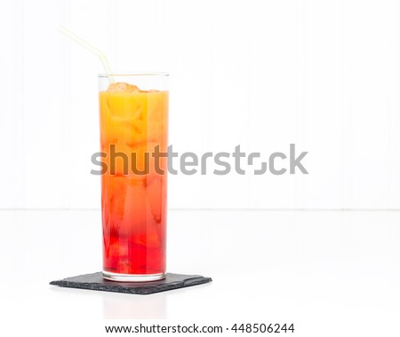 Tropical cocktail known as a tequila sunrise in a tall glass. - stock photo