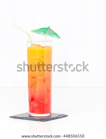 Tropical cocktail known as a tequila sunrise in a tall glass with ice. - stock photo