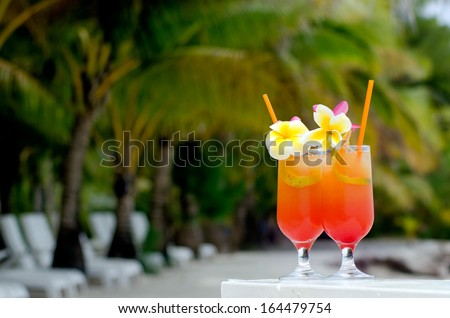 Tropical cocktails served outdoor on Pacific Island resort with Coconut Palm trees in the background. - stock photo