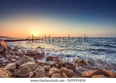 Tropical colorful sunrise at the stones beach - stock photo