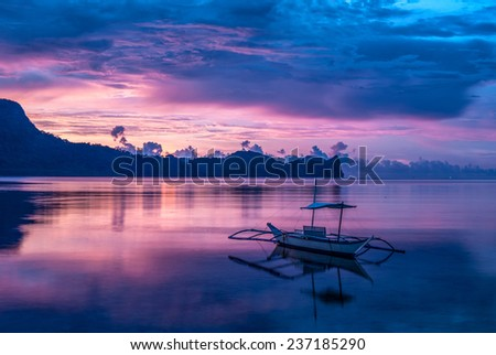 Tropical colorful sunset with a banca boat in El Nido, Palawan - Philippines - stock photo