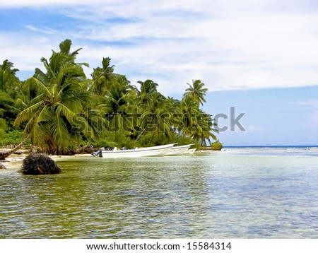 Tropical cove surrounded with palm trees.  Beautiful clear water with boats parked by shoreline. - stock photo