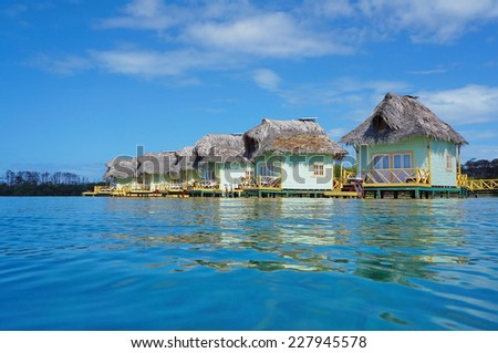 Tropical eco resort with thatched overwater bungalows, Caribbean sea, Bocas del Toro, Panama, Central America - stock photo